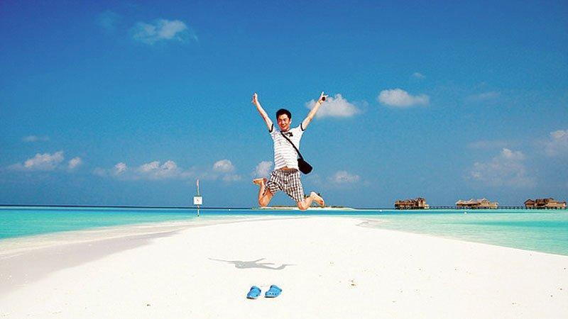 Jumping on a beautiful white sandy beach, Maldives