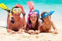 Children in snorkelling gear on a beach in Thailand