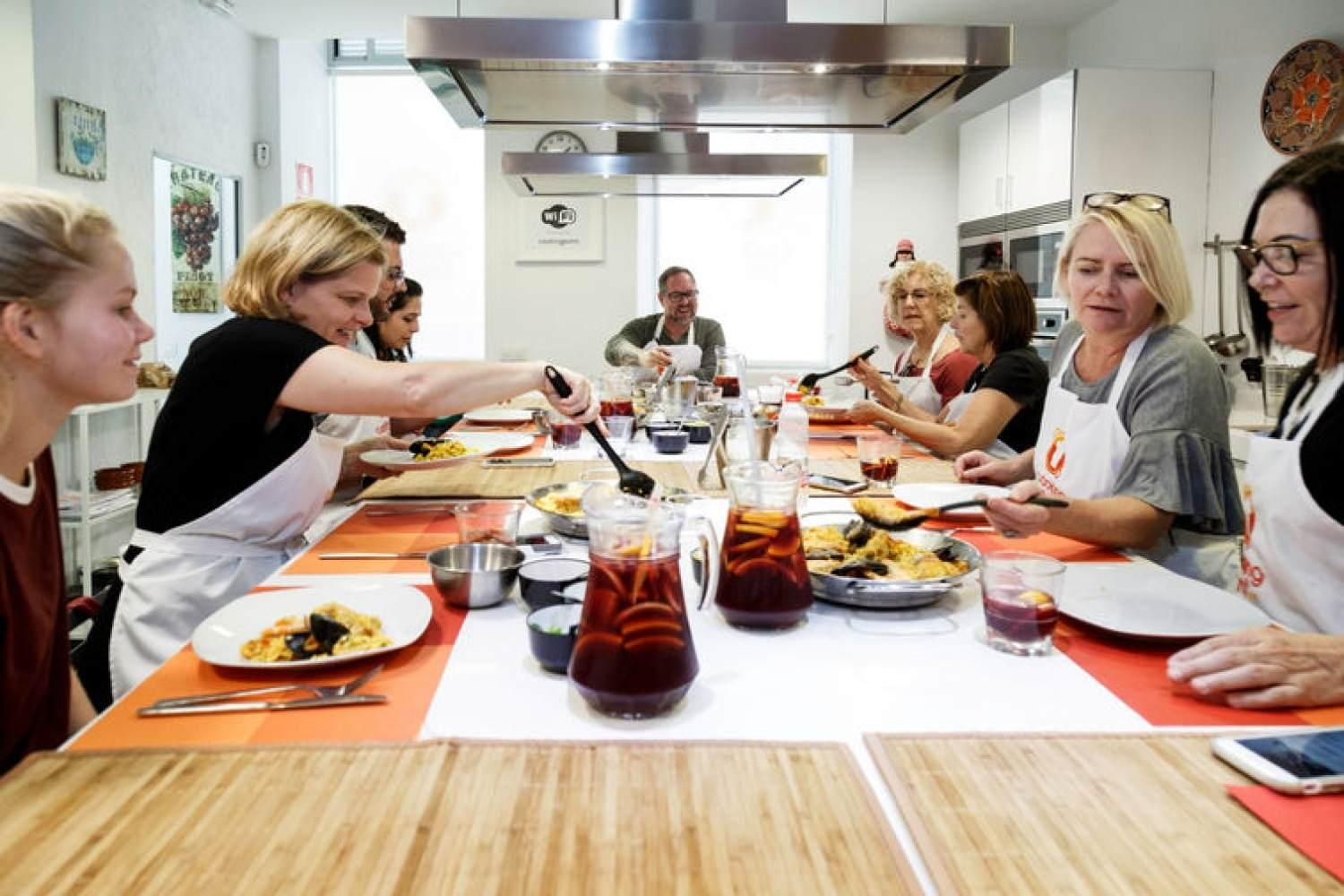 Group having fun during a paella cooking class in Madrid